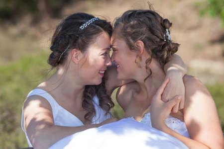Photo pour two brides smile and embrace in nature surroundings on sunny day - image libre de droit