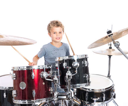 Photo for young blond caucasian boy plays drums in studio against white background - Royalty Free Image