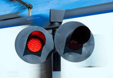 Foto per flashing red lights while white train passes railway crossing - Immagine Royalty Free