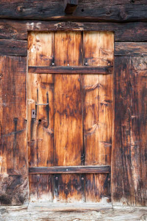 Photo pour closeup of very old grungy brown wooden weathered planks of door in ancient swiss barn - image libre de droit