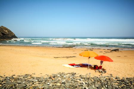 Photo pour Beach umbrellas in the sand at beach Praia do Vale dos Homens near Aljezur, Algarve Portugal - image libre de droit
