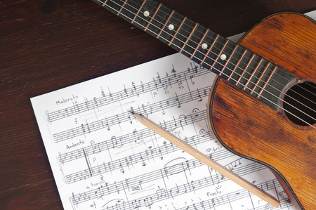 Photo for Music notes, vintage guitar and two pencils on table - Royalty Free Image