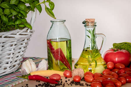 Foto de Bottles with flavored oil. Tastes of Italy. Basil, pepper and garlic. Preparing a salad.. Tomatoes and flavors of pizza. - Imagen libre de derechos
