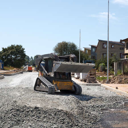 Photo pour construction of a new street. mini excavator bobcat mowing breakstone - image libre de droit