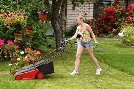 Foto de Woman cuts the grass with an electric lawn mower - Imagen libre de derechos