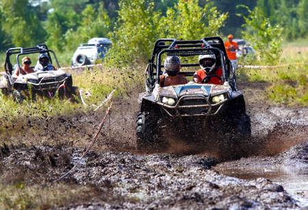 Foto de An ATV sprays mud as it zips around a corner in a dirt road rally - Imagen libre de derechos