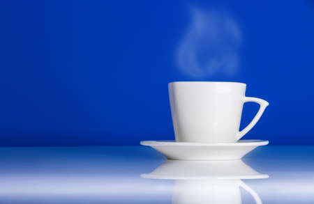 White cup of hot coffee on blue background with reflection