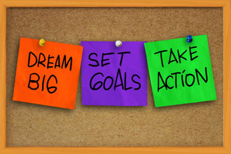 Foto de The words Dream Big, Set Goals, Take Action written on sticky colored paper over cork board - Imagen libre de derechos
