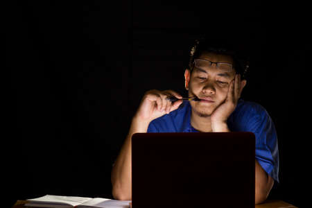 Foto de Young man thinking hard in front of his laptop in the dark - Imagen libre de derechos