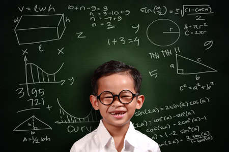 Foto de Little genius Asian student boy with glasses smiling over green chalkboard with math equivalents written on it - Imagen libre de derechos