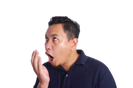 Foto de Photo image of funny Asian man checking his own bad mouth smell odor, dental health problem, isolated on white - Imagen libre de derechos
