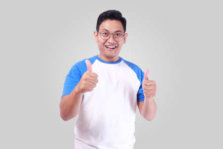 Photo for Photo image portrait of funny attractive cute young Asian man in white shirt smiling and showing thumb up sign while standing over grey background - Royalty Free Image
