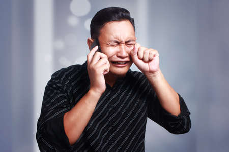 Attractive young Asian man talking on his phone, getting bad news, shocked and crying gesture