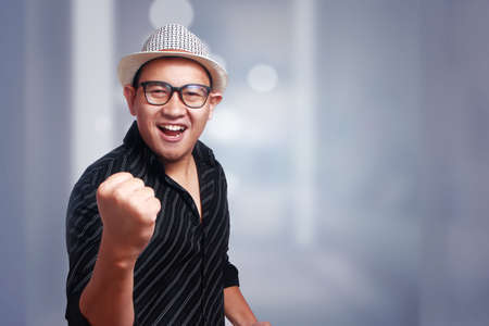 Photo for Funny attractive cute Asian man wearing eyeglasses and panama hat smiling winning gesture - Royalty Free Image
