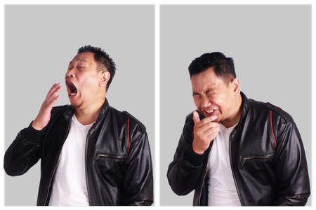 Foto de Portrait of funny young Asian man wearing black leather jacket sneezing, over grewy background - Imagen libre de derechos