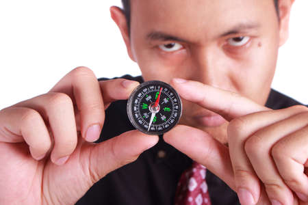 Portrait of young businessman showing compass, focus on compass with blurred face, business direction concept