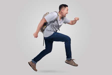 Foto de Attractive young Asian man worried and running fast to be late - Imagen libre de derechos