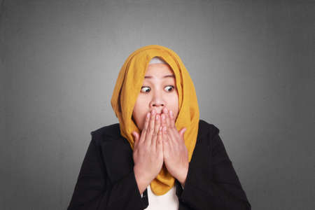 Photo pour Young attractive muslim businesswoman wearing hijab covering her mouth with hands, shocked surprised expression - image libre de droit