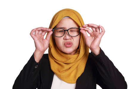 Photo pour Portrait of muslim businesswoman wearing hijab adjusting her eyeglasses trying to see focus, eye sight trouble, blur vision, isolated on white - image libre de droit