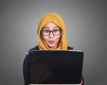 Photo for Portrait of muslim businesswoman wearing hijab using laptop with shocked surprised excited facial expression gesture - Royalty Free Image