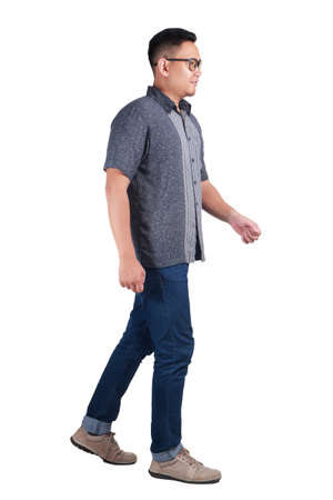 Photo for Full body portrait of young Asian man wearing batik shirt and glasses walking side view and smiling, isolated on white - Royalty Free Image