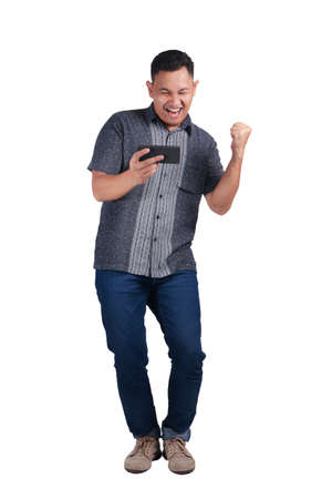 Foto de Young Asian man wearing blue jeans and batik shirt playing his phone with a happy expression. Isolated on white. Full body portrait - Imagen libre de derechos