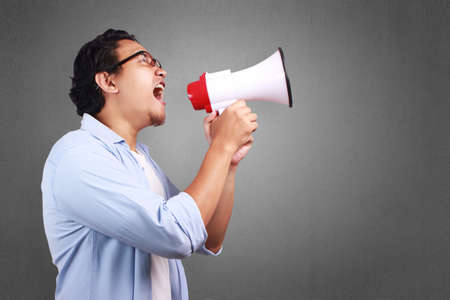 Photo pour Young Asian man wearing white and blue shirt shouting using megaphone, angry expression. Close up body portrait - image libre de droit