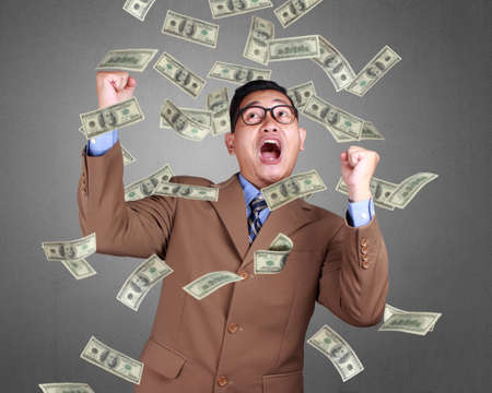 Foto de Young Asian businessman wearing suit winning gesture. Close up body portrait. Money falling sign - Imagen libre de derechos