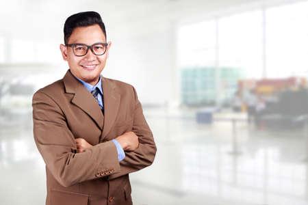 Foto de Young Asian businessman wearing suit and glasses smiling looking at a camera, crossed arm - Imagen libre de derechos