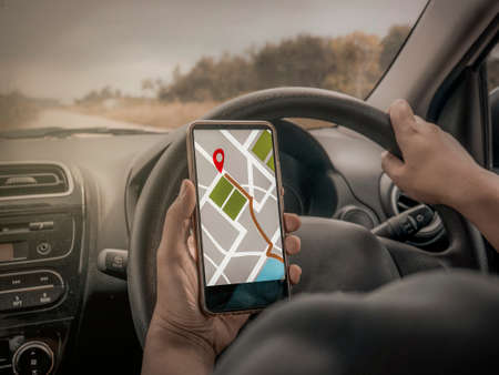 Foto de Car driver using smart phone with GPS map navigation while driving, car sharing app concept - Imagen libre de derechos