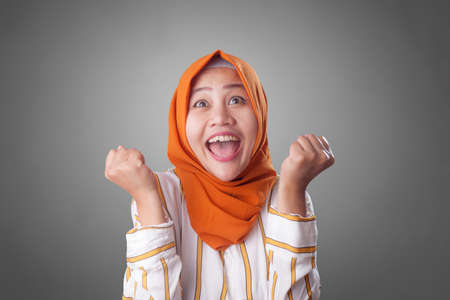 Photo pour Portrait of success beautiful muslim businesswoman wearing hijab showing winning victory gesture over gray background - image libre de droit
