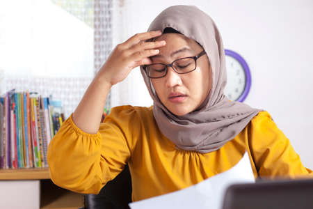 Photo pour Portrait of Asian muslim businesswoman working on laptop at the office, tired sick stress headache gesture because of overworked, ramadan fasting concept - image libre de droit
