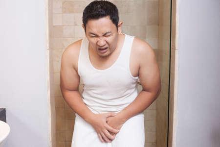 Photo pour Portrait of young Asian man having pain problem in his genital area, urinary problem concept - image libre de droit