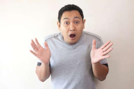 Foto de Portrait of Young asian men in casual grey shirt, shocked gesture with open mouth. Hands rised up - Imagen libre de derechos