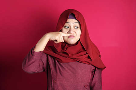 Photo pour Portrait of cute funny Asian muslim lady wearing hijab close her nose because of bad disgusting smell odor, against red background - image libre de droit