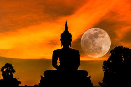 Photo pour silhouette big buddha statue sitting in sunset with full moon background - image libre de droit