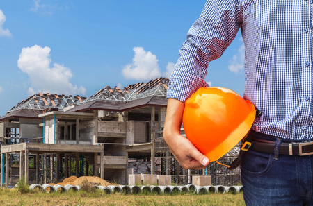 Photo pour engineer holding yellow safety helmet in construction new home housing development background - image libre de droit