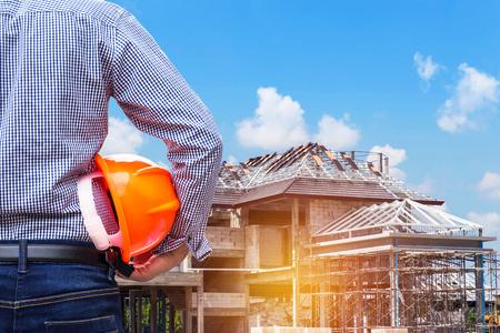 Foto de resident engineer holding yellow safety helmet at new home building under construction site - Imagen libre de derechos