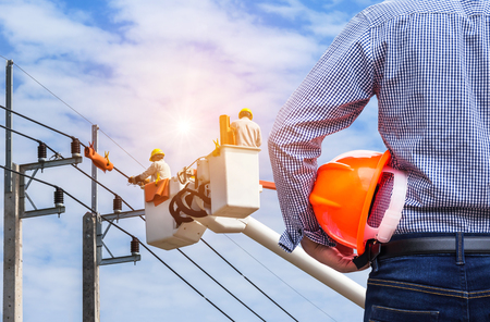 Photo pour Electrical engineer holding safety helmet with electrician working on electric power pole with  bucket hydraulic lifting platform on blue sky background - image libre de droit
