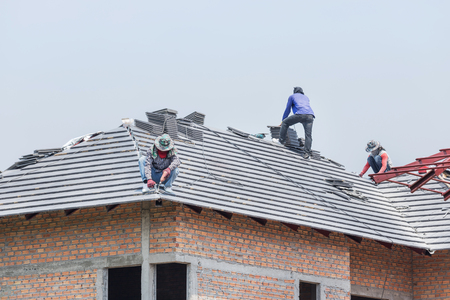 Photo for Workers installing concrete tiles on the roof while roofing house - Royalty Free Image