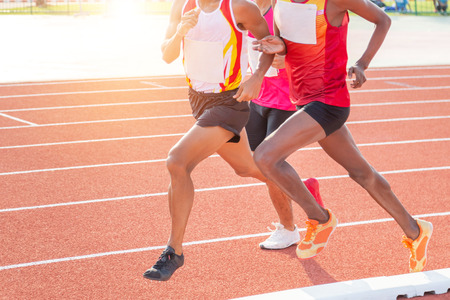 Photo pour Close up movement athletes sprint running on running track during race athletics competition in stadium - image libre de droit