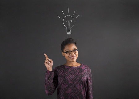 Photo pour South African or African American black woman teacher or student with a good idea or answer lighbulb standing against a chalk blackboard background inside - image libre de droit