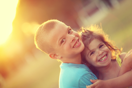 Brother and sister in hug with love and big happy smile. Shalow depth of field. Soft focus.