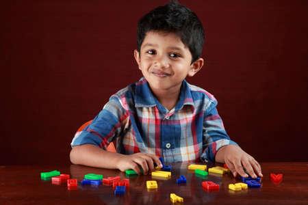 Foto de A small kid looks as he plays with toy alphabets in dark background - Imagen libre de derechos