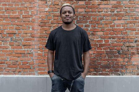 Foto de Young attractive dark-skinned man in black T-shirt on red bricked background. - Imagen libre de derechos