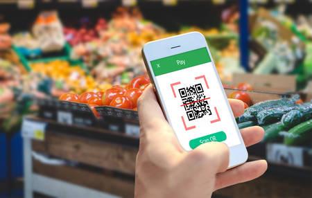 Photo pour Hand holding smartphone to scan QR code payment , online shopping , cashless technology concept.  - image libre de droit