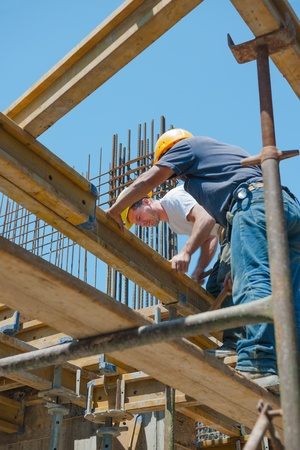 Photo pour Authentic construction workers placing slab formwork beams in construction site - image libre de droit