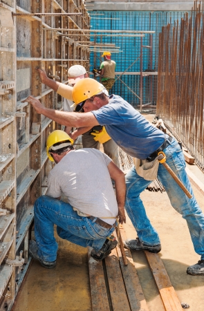 Photo pour Authentic construction builders working together for positioning concrete formwork frames in place - image libre de droit