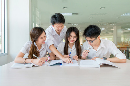 Photo pour Group of asian students in uniform studying together at classroom - image libre de droit