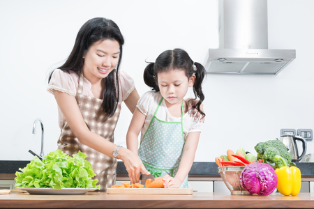 Photo pour family, children and happy people concept - Asian mother and kid daughter cooking in the kitchen at home - image libre de droit